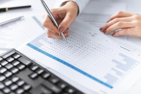 foto van vrouw hand schrijven op papier met getallen Stockfoto