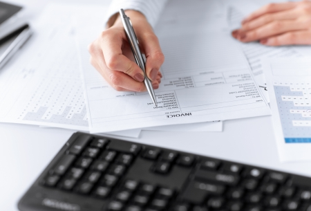 remit: picture of woman hand filling in invoice paper Stock Photo