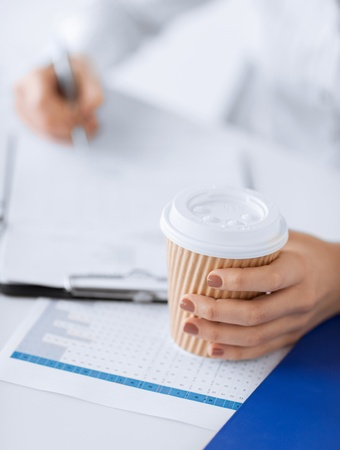 picture of woman hand filling in blank paper and drinking coffee photo