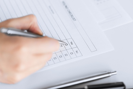 answering: close up of woman hand with blank questionnaire or form Stock Photo