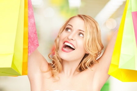 attractive woman holding color shopping bags in mall Stock Photo - 20557325