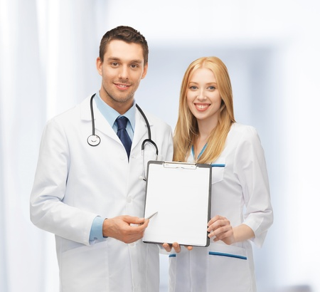 bright picture of two young attractive doctors pointing at blank paper photo