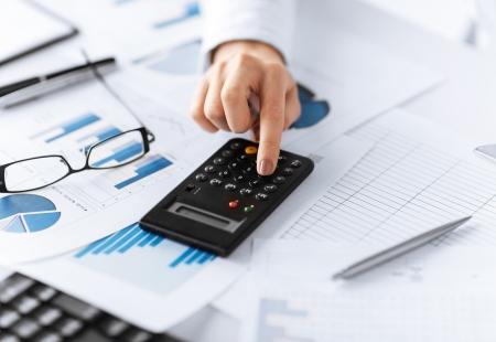 salarios: imagen de la mano de la mujer con la calculadora y documentos Foto de archivo