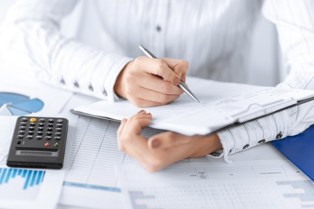 accountancy: picture of woman hand with calculator and papers Stock Photo