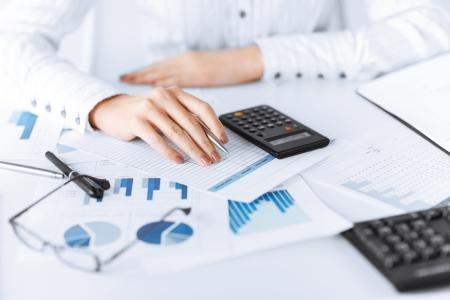 Photo de la main de femme avec la calculatrice et papiers Banque d'images - 20557155