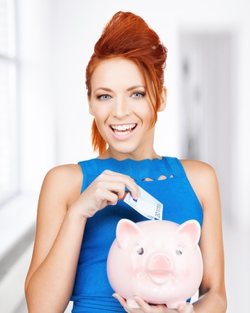 happy businesswoman putting cash money into piggy bank photo