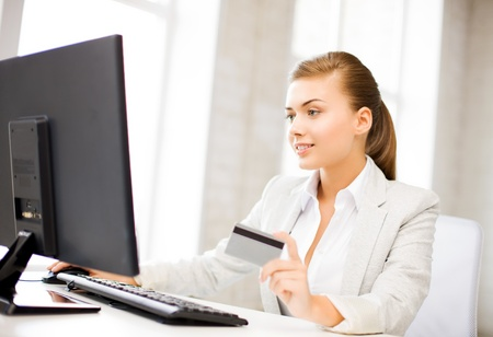 smiling businesswoman with computer using credit card photo