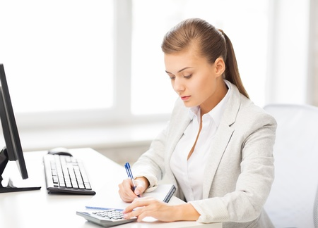 accountants: picture of businesswoman with notebook and calculator Stock Photo
