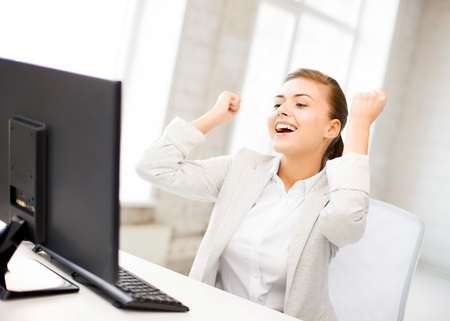 accountant: picture of happy businesswoman with computer in office