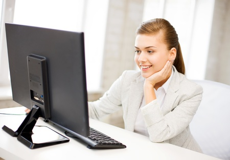 picture of smiling businesswoman with computer in office