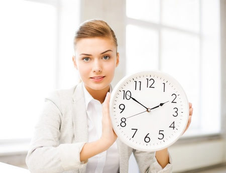 picture of attractive businesswoman showing white clock photo