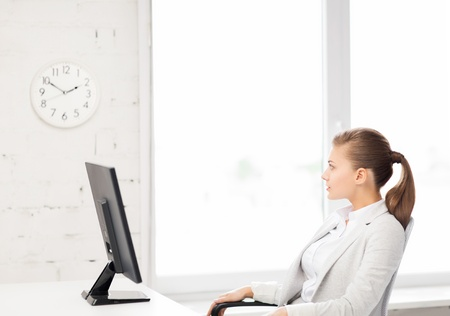 career timing: picture of businesswoman looking at wall clock in office Stock Photo