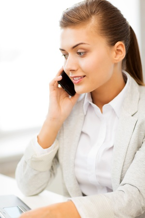 picture of smiling businesswoman with smartphone in office photo