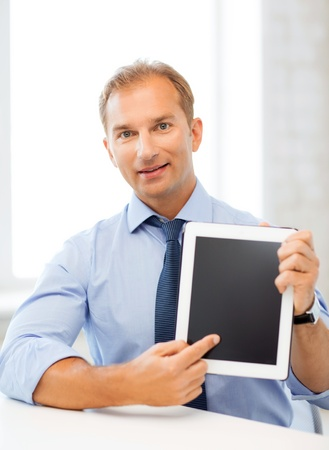picture of smiling businessman with tablet pc in office photo
