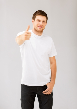 happy man in blank white t-shirt showing thumbs up