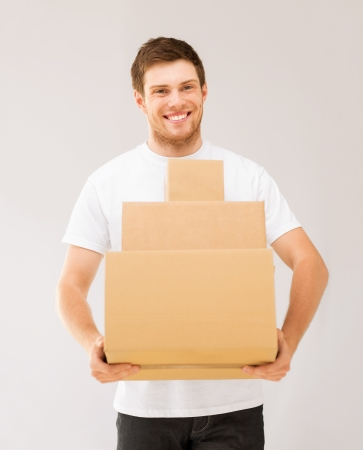 man carrying box: picture of smiling man carrying carton boxes
