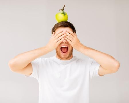 nice food: кричать молодой человек с зеленым яблоком на голове Фото со стока
