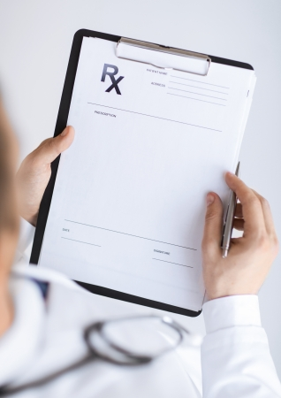 clipboards: close up of male doctor writing prescription paper