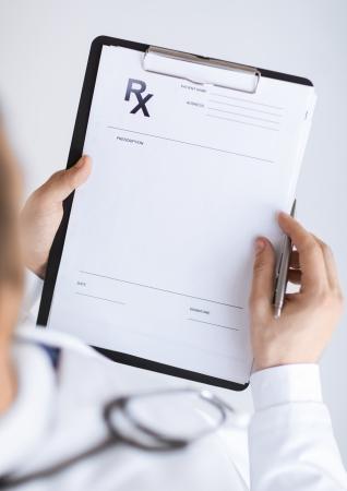 close-up van mannelijke arts schrijven recept papier Stockfoto