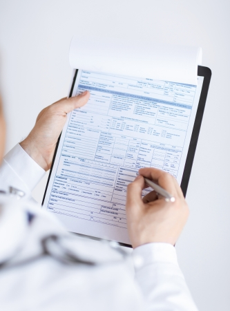 prescribing: close up of male doctor holding prescription paper in hand