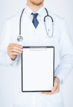 close up of doctor holding blank white paper photo