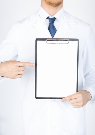 close up of doctor pointing at blank white paper photo