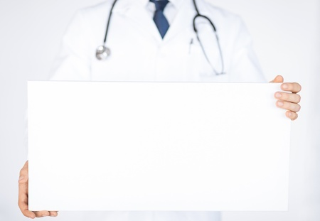 close up of doctor holding blank white banner photo