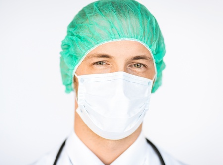 picture of half face of surgeon in medical cap and mask photo