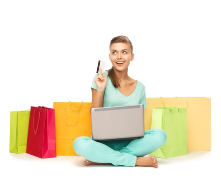 ノート パソコン、買い物袋、クレジット カードを持つ女性