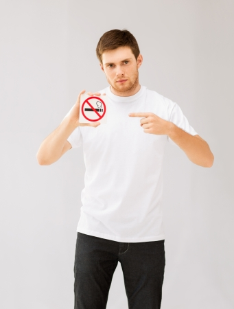 picture of young man pointing at no smoking sign photo