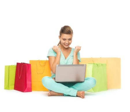 gelukkige jonge vrouw met laptop en boodschappentassen
