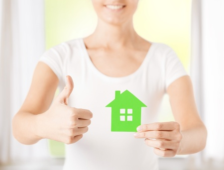 woman hands holding green house showing thumbs up photo