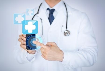 医療アプリでスマート フォンを保持している男性の医者のクローズ アップ
