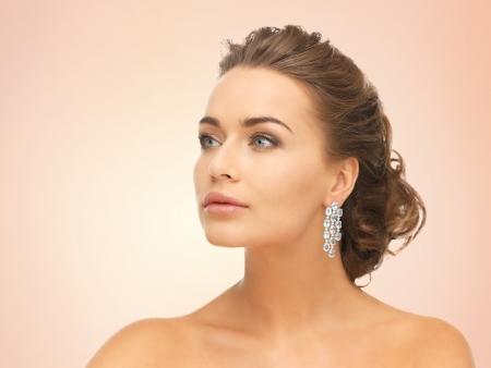close-up van mooie vrouw dragen glimmende diamanten oorbellen