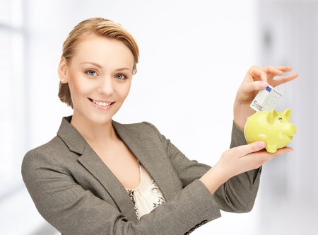 happy businesswoman putting cash money into small piggy bank photo