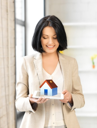 digi: picture of woman holding tablet pc with house illustration Stock Photo