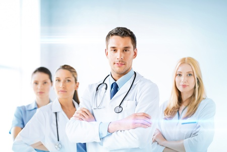 family doctor: attractive male doctor in front of medical group Stock Photo