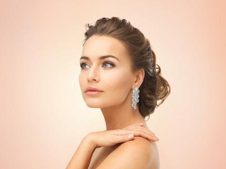 schöne frauen: Nahaufnahme der schönen Frau trägt glänzende Diamant-Ohrringe