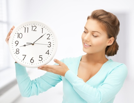 attractive woman holding wall clock in her hands photo