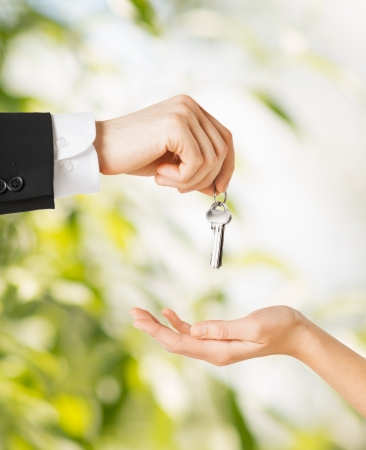 property agent: picture of man hand passing house keys to woman Stock Photo
