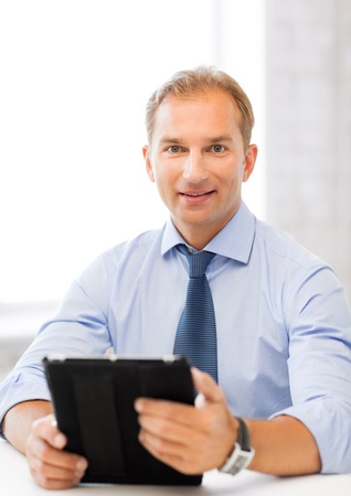 handsome businessman with tablet pc in office photo