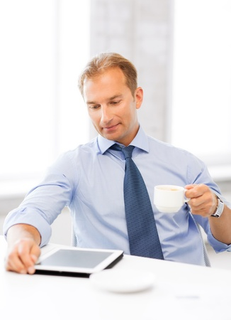 smiling businessman with tablet pc drinking coffee in office photo