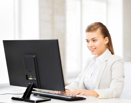 picture of smiling businesswoman with computer in office photo