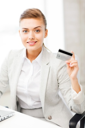 smiling businesswoman with laptop showing credit card Stock Photo - 20611545