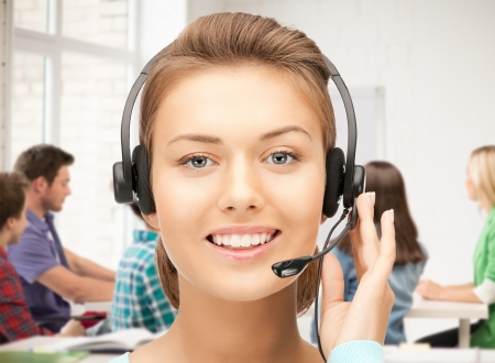 call girl: friendly female helpline operator with headphones in office Stock Photo