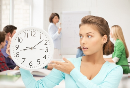 time to work: bright picture of girl holding big clock at school