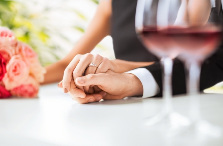 ring wedding: picture of engaged couple with wine glasses in restaurant Stock Photo