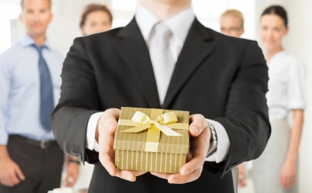 giving gift: close up of man hands holding gift box in office