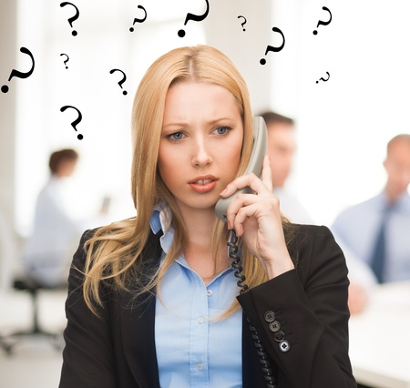 landline: bright picture of confused woman with phone in office Stock Photo
