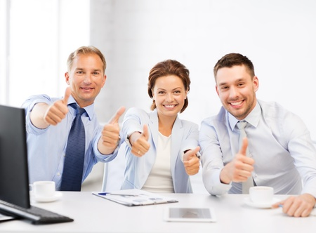 having a break: friendly business team showing thumbs up in office Stock Photo